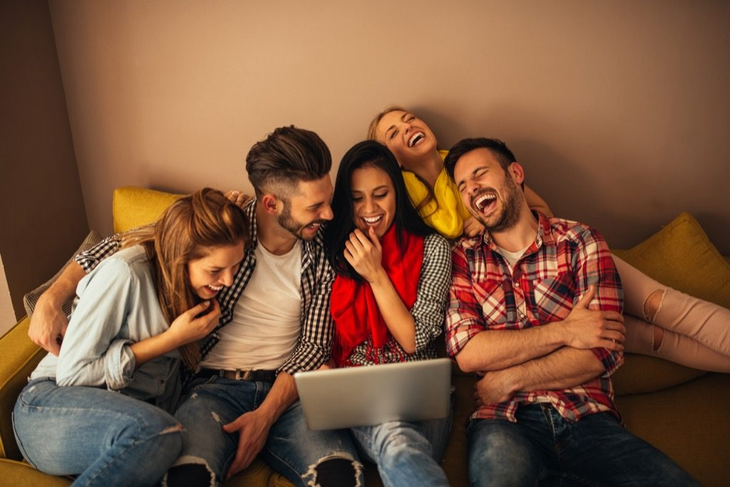 group of friends laughing together around a laptop, signs your husband is cheating