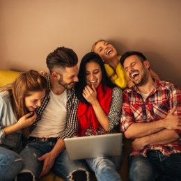 group of friends laughing at computer, bad jokes