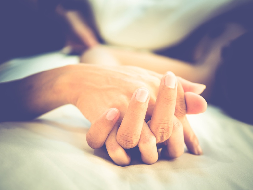 this couple holding hands on a bed implies that they're having sex!