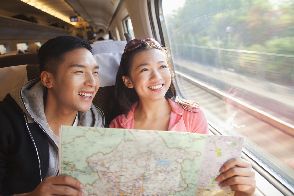 young asian man and young asian woman holding a map and looking out the window on a train