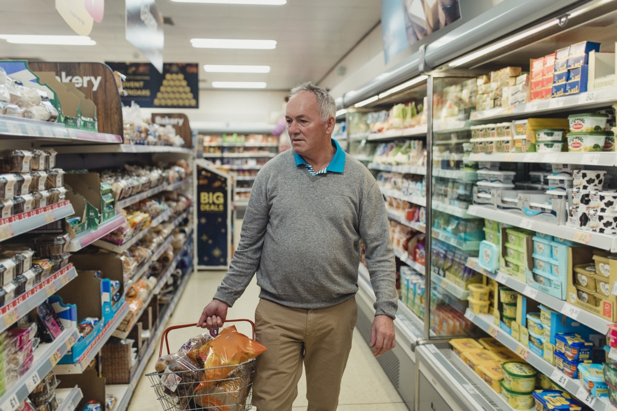 older white man holding a basket and looking at the food while wandering down the aisle of a grocery store