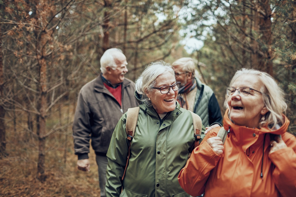 two older white women and two older white men hiking outdoors