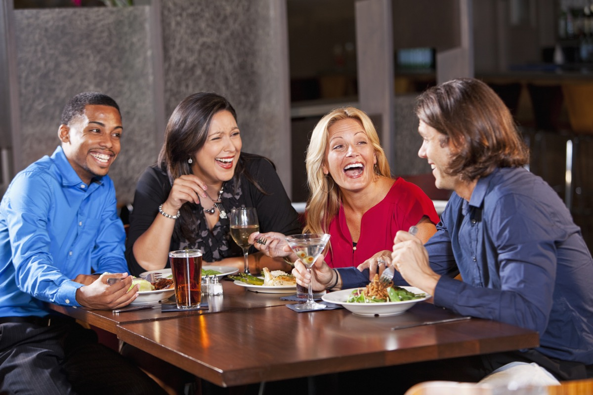 two couples sitting around a table and laughing on a double date