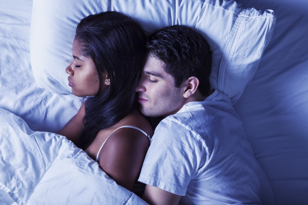 close up of black woman being held from behind by white man in bed