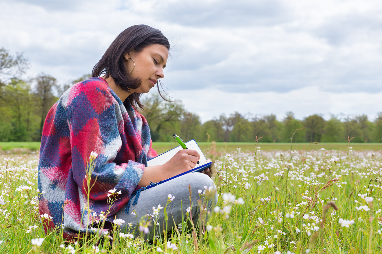 latina woman writing in a journal in a meadow