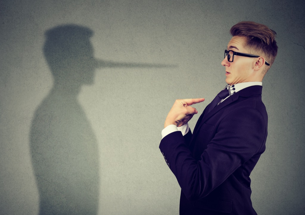 Man points finger at himself while his shadow shows a long nose, signs someone is lying