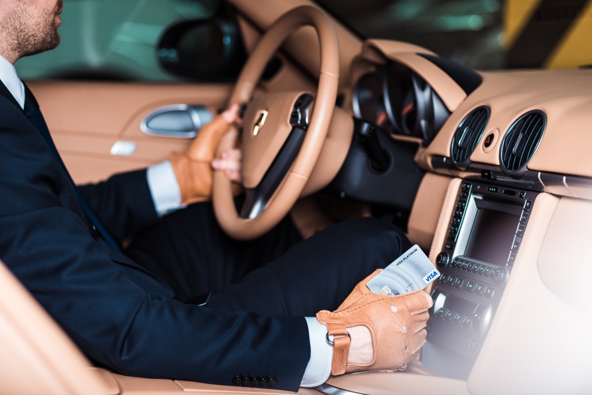interior shot of a man wearing a suit and sitting behind the wheel of a porsche 911 turbo
