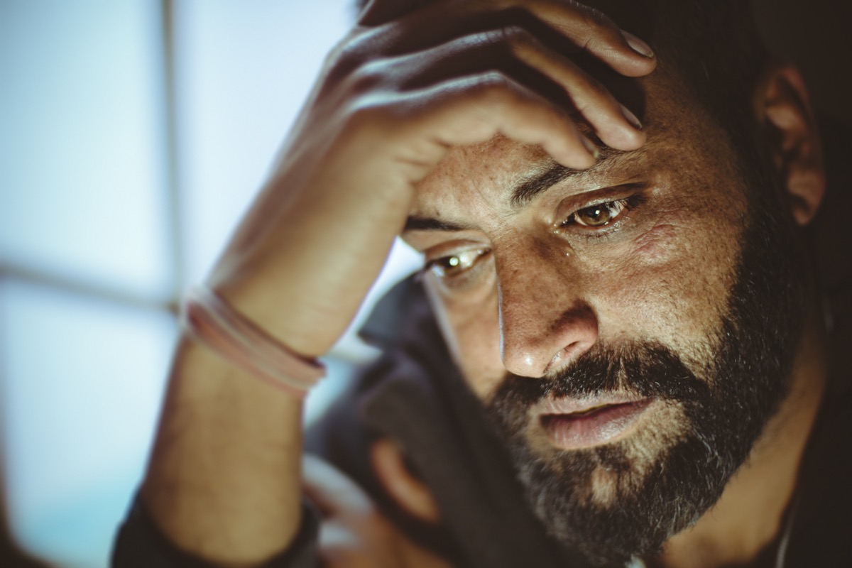 Indoor close-up image of disturbed, sad, Asian, Indian mid adult man with strong character and facial hair. He is sitting at home near door in day time. He is crying and a drop of tear coming out of his eye. He is looking down and holding his head while thinking something deeply with blank expression.