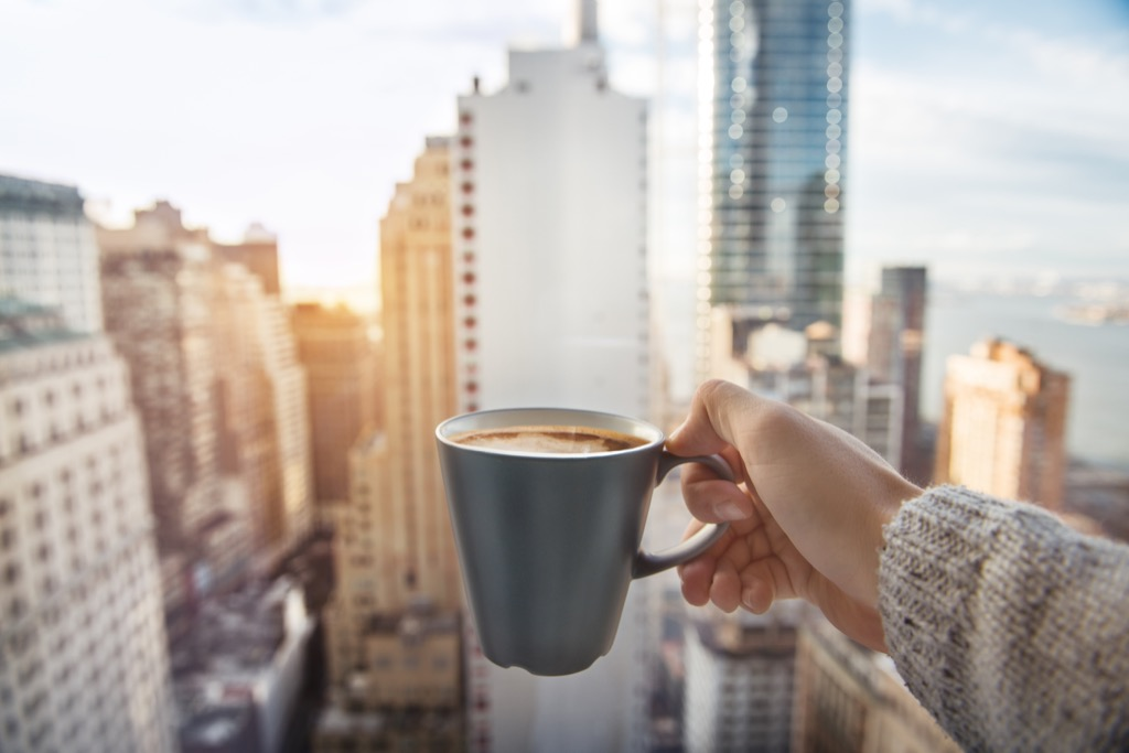 a cup of coffee in front of the manhattan new york skyline