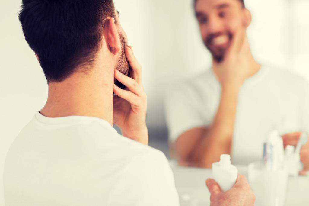 a well-groomed man stroking his beard in the bathroom