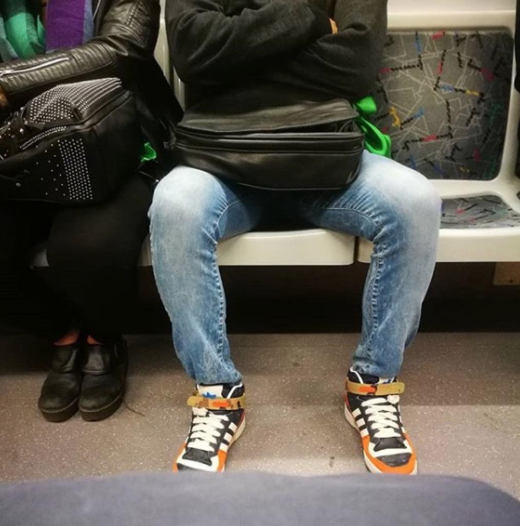 Man manspreading on the subway, city