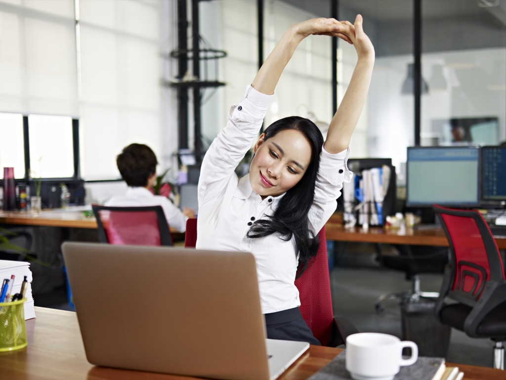 Woman being mindful and taking a deep breath at her desk