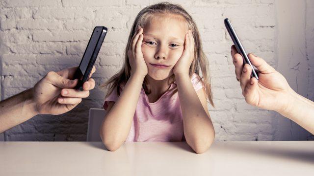 child sulks at parents flip through phones.