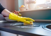 white person wearing gloves cleaning counters with sponge