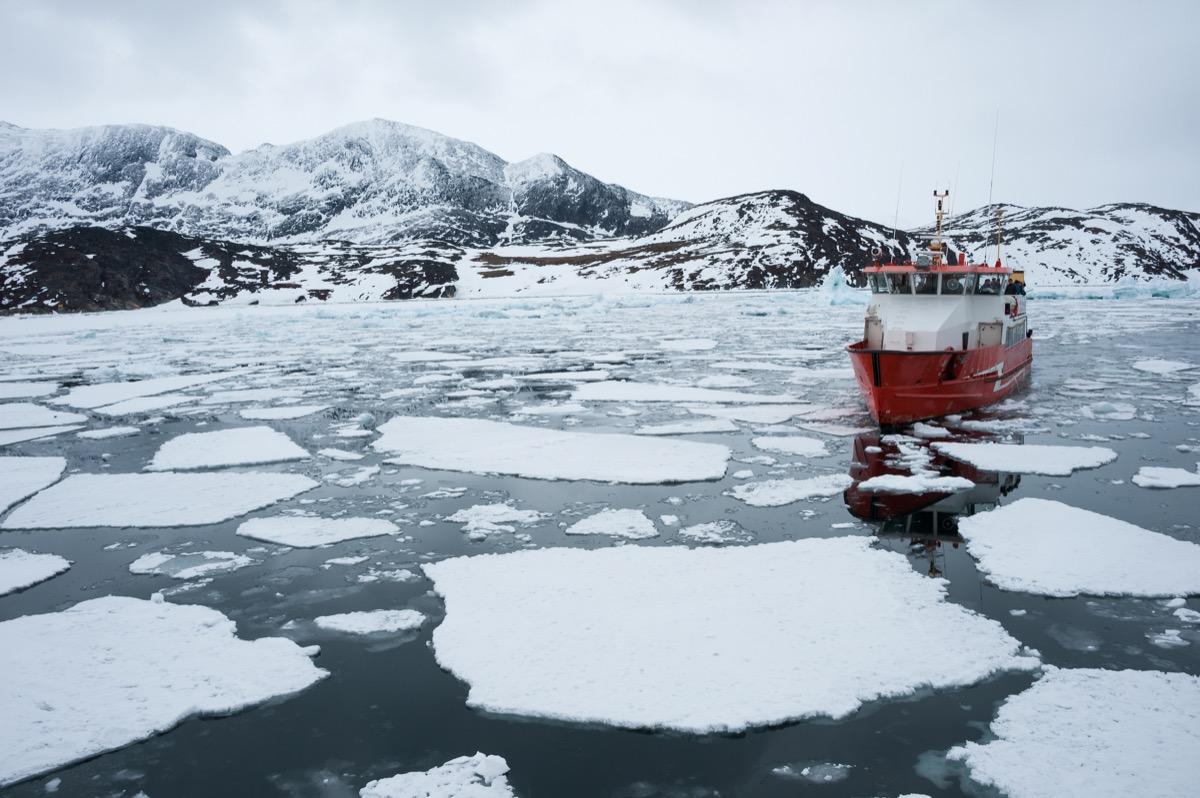 Ship sailing through icy ocean in Greenland