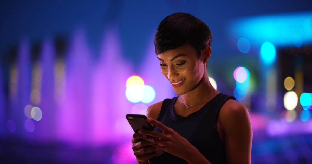 young black woman texting and smiling outside at night