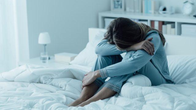 woman alone on bed sad