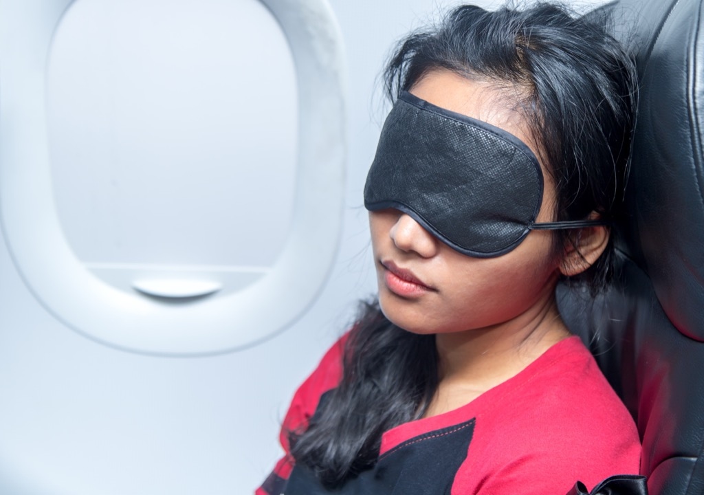 Woman sleeping on a plane with a face mask.