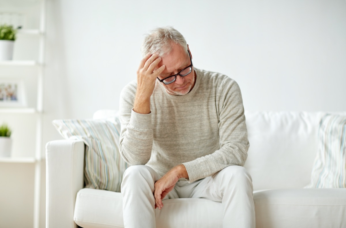 older man sits on a couch and holds his head from stress