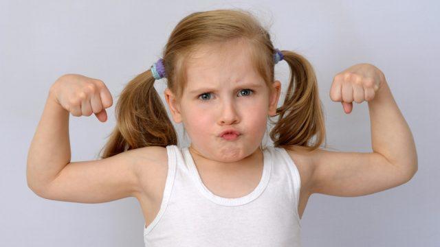strong little girl flexing