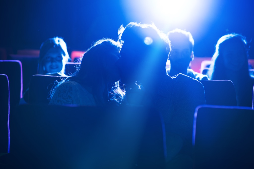 couple kisses at movie theater