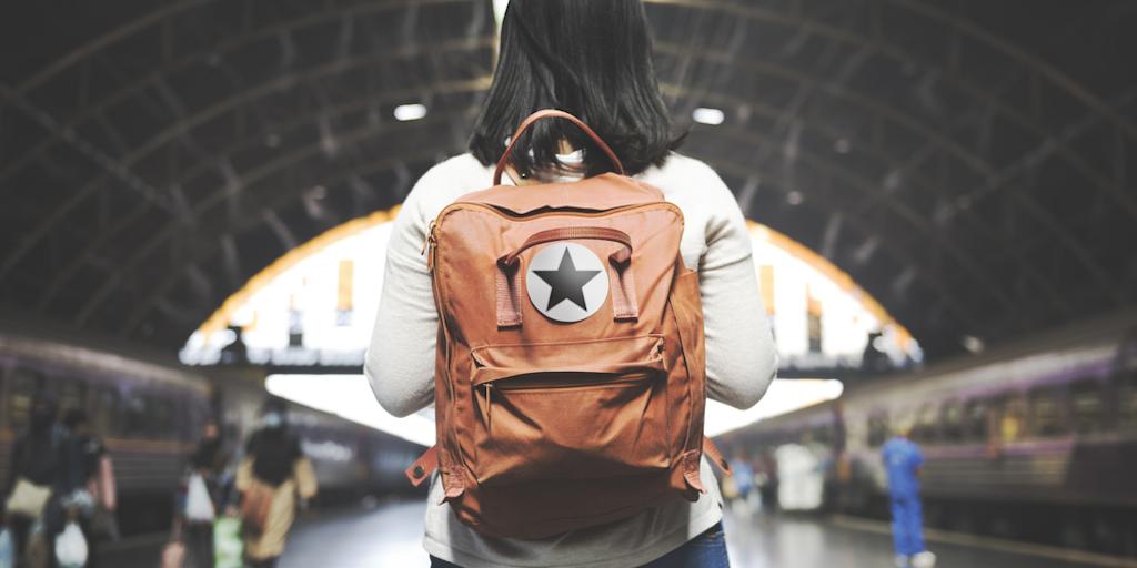 woman wears backpack on train