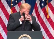trump uses two hands to hold glass of water