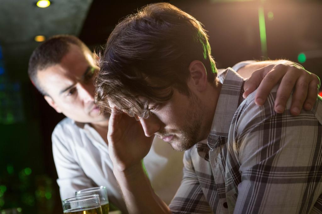 man checks on stressed friend at bar