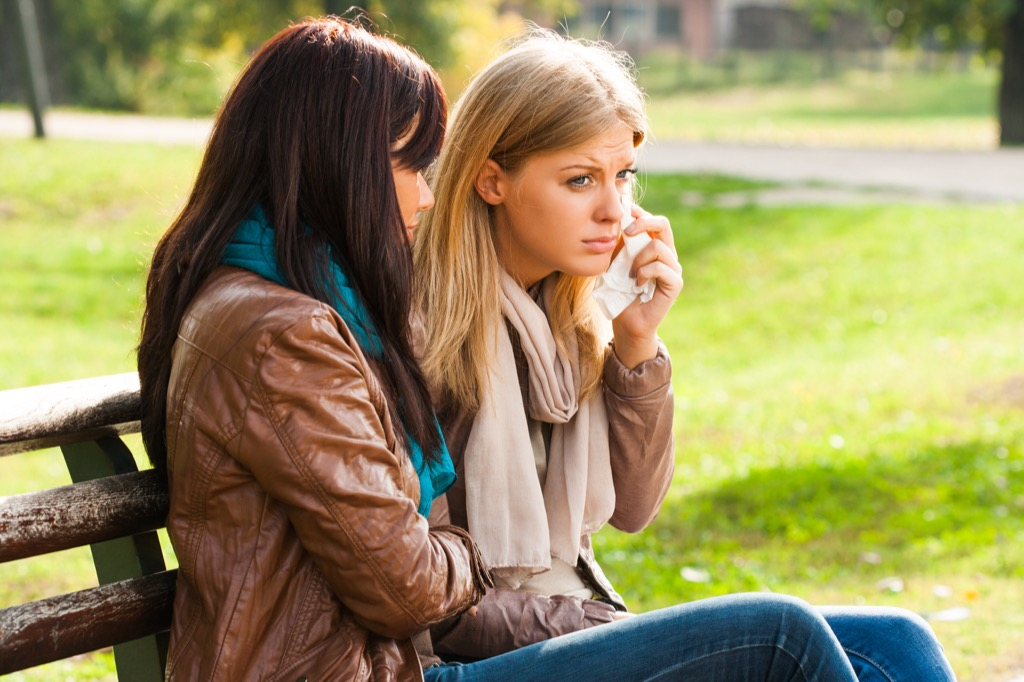 woman comforts crying friend on bench {Benefits of Crying}