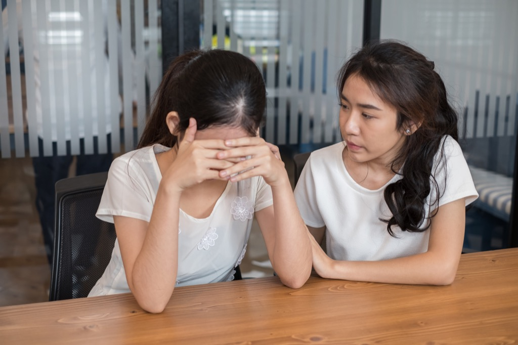 girl comforts friend with head in hands