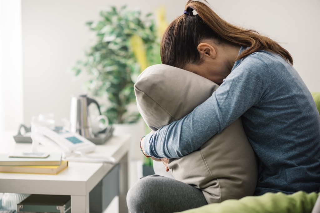 woman alone on couch crying into pillow {Holiday Depression}