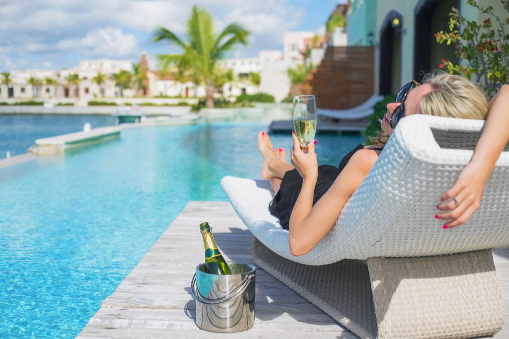 woman drinking by the pool