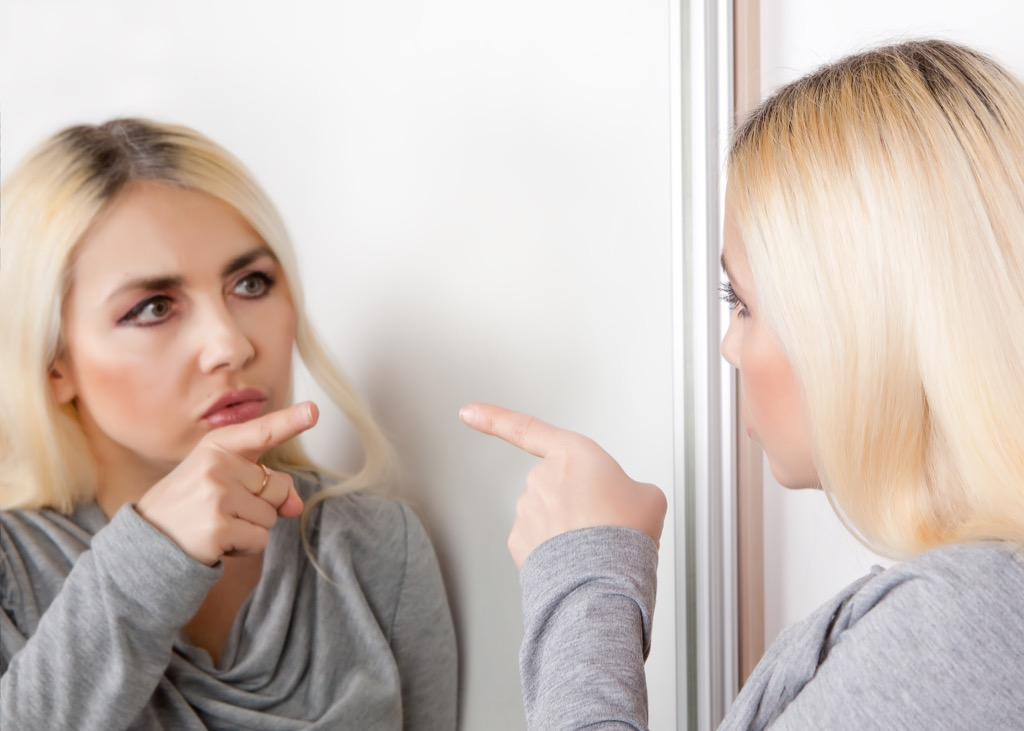 Woman yelling at herself in the mirror
