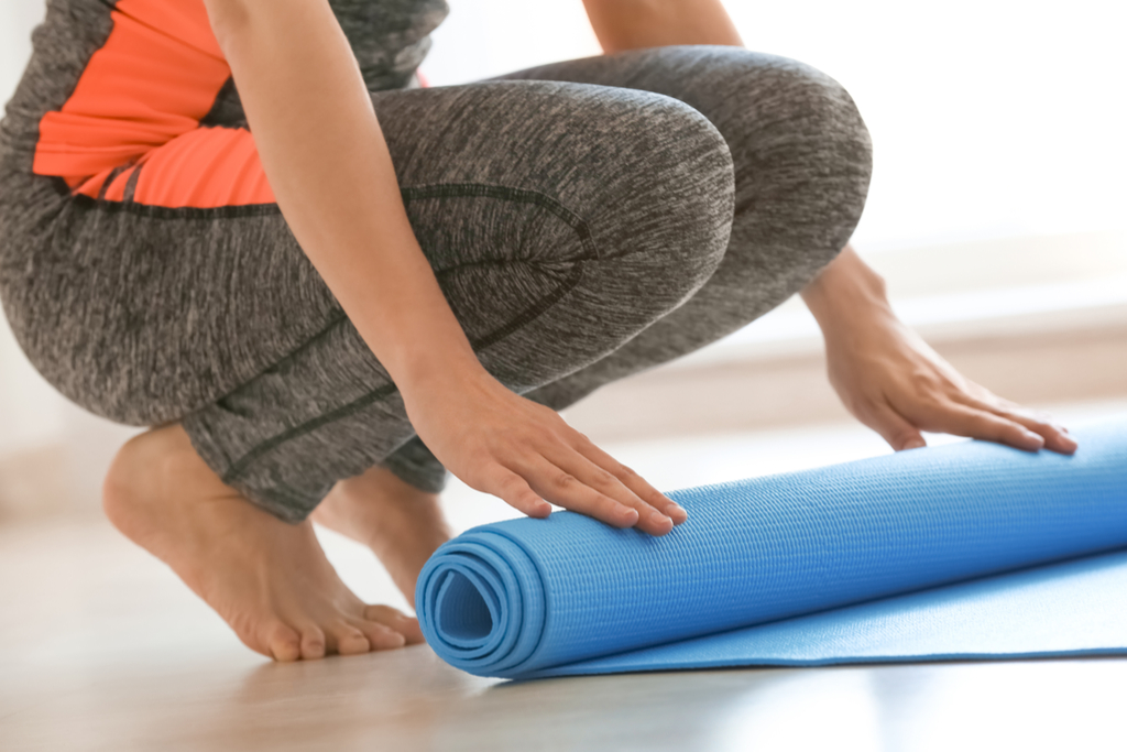 Woman Rolling Up Yoga Mat House Cleaning
