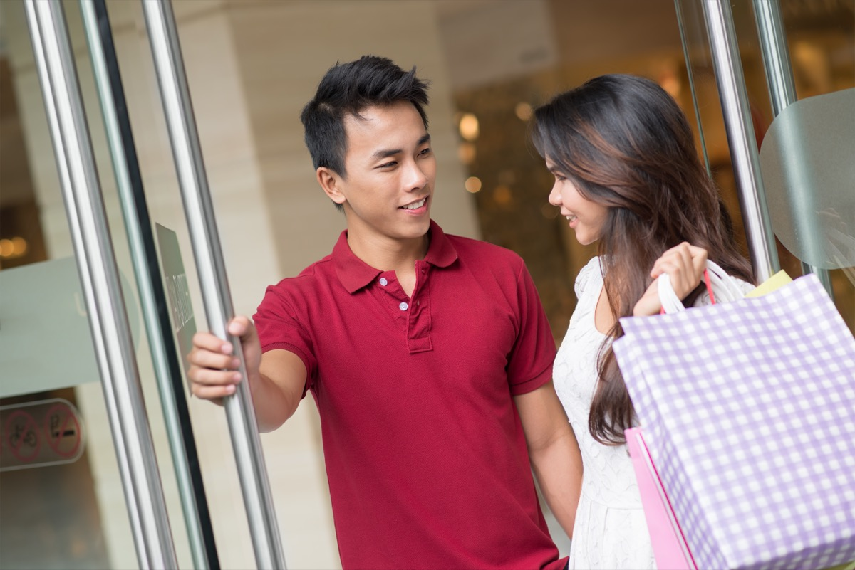 young asian man holding door for woman while shopping