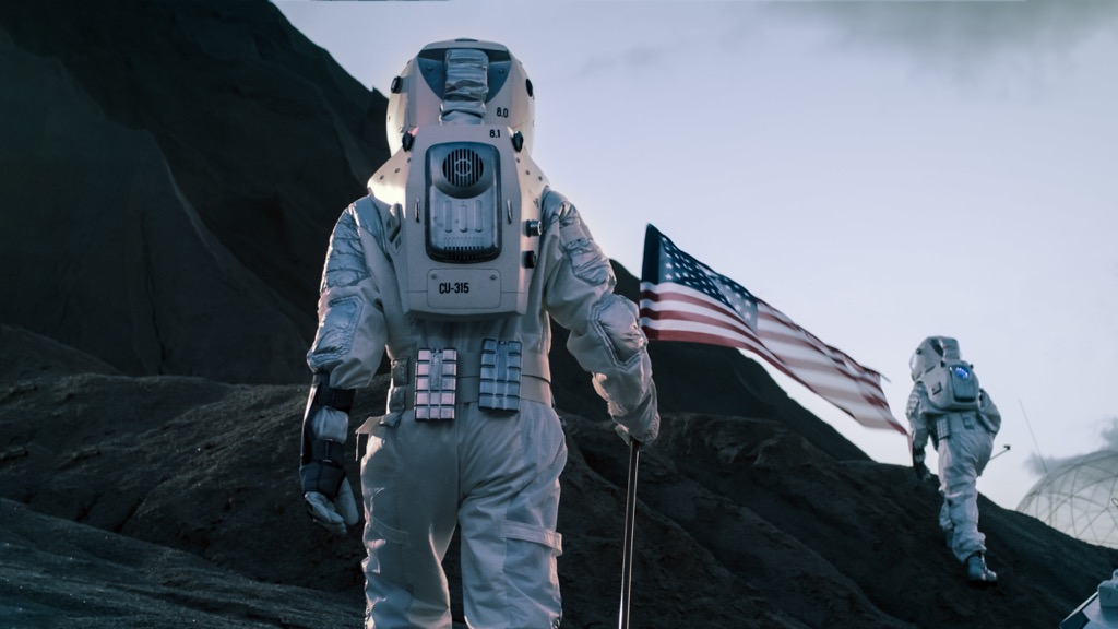 astronaut walking on moon with american flag 27 Insane Things Astronauts Have to Do