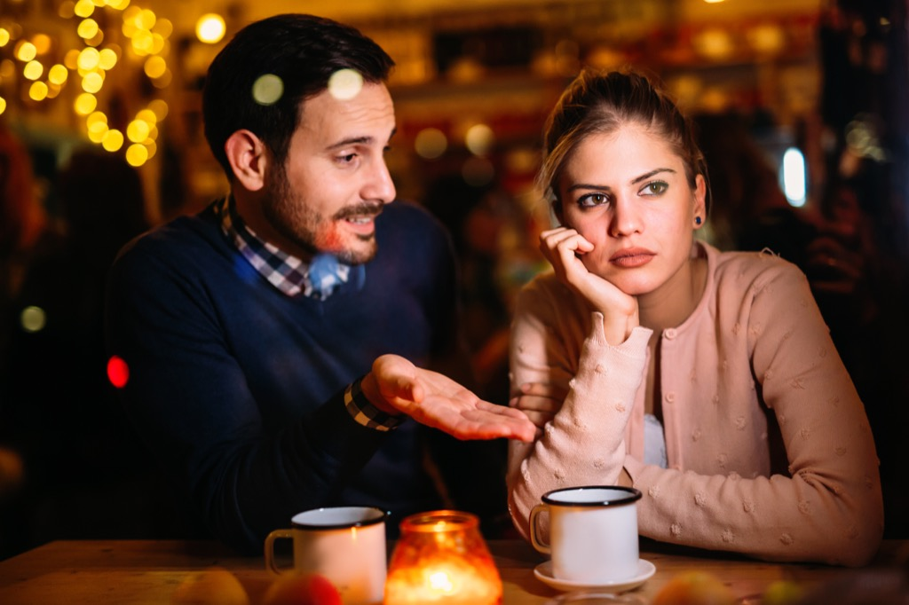 couple in an argument at dinner table in a restaurant, signs your husband is cheating
