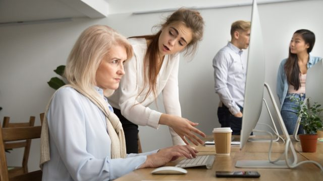 woman looking angry at older coworker on computer
