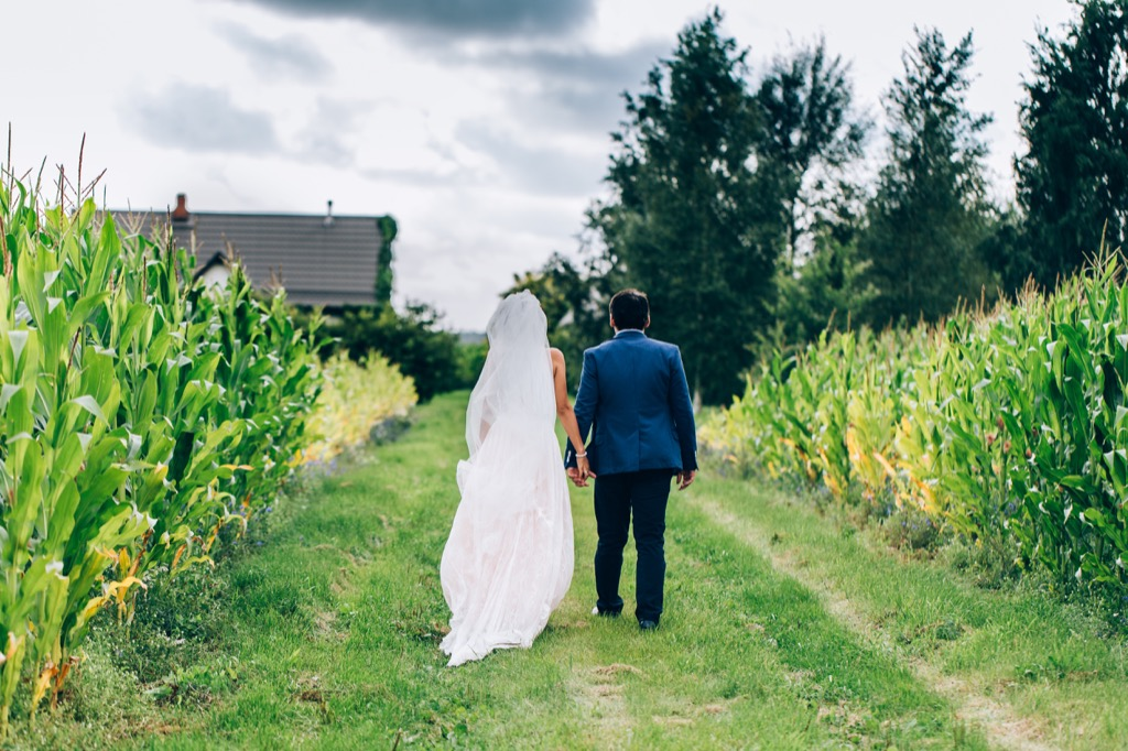 bride and groom walking through cornfield This Is the Age Most People Get Married in Every U.S. State