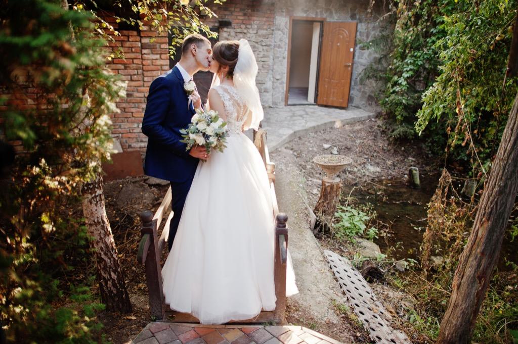 bride and groom kissing forest https://www.shutterstock.com/image-photo/bride-groom-go-home-along-road-1140990437?src=https://bestlifeonline.com/wp-content/uploads/sites/3/2018/07/bride-groom-kissing-forest.jpg?quality=82&strip=all