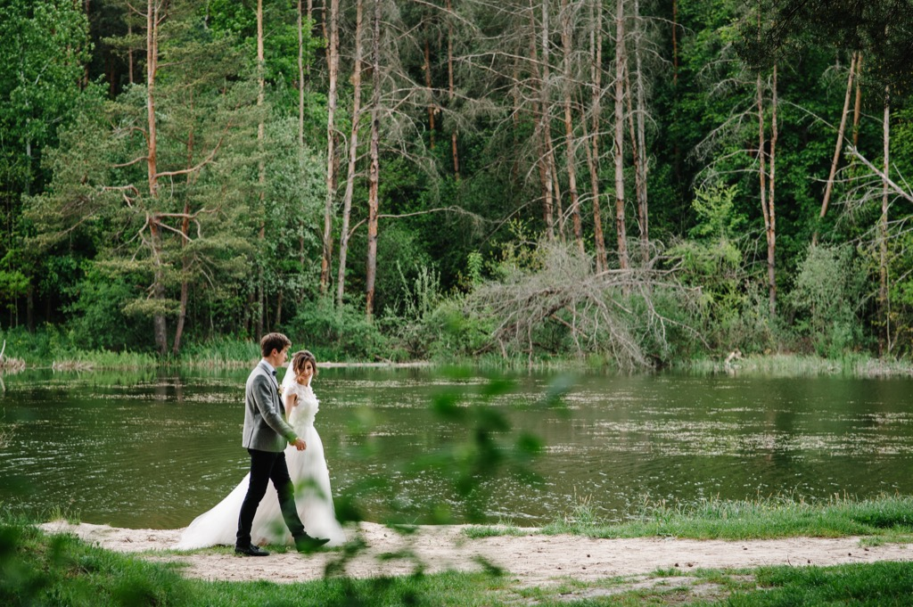 bride and groom walking through nature this is the age most people get married in every US state