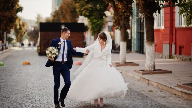 bride and groom walking on a street