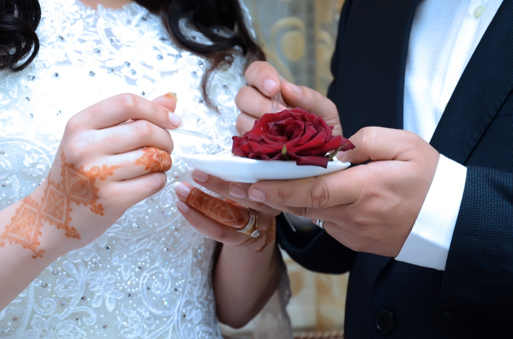 bride and groom eating wedding cake this is the age most people get married in every US state