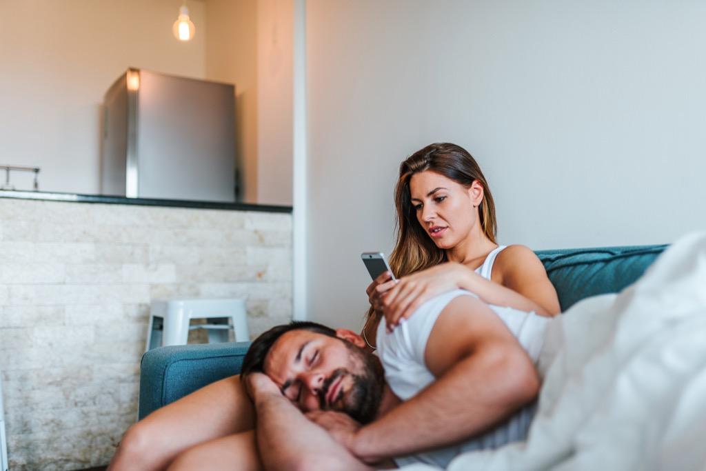 Girlfriend checking her boyfriend's phone while he sleeps