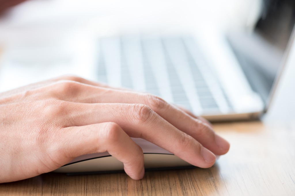 Man clicking on a mouse by the computer.