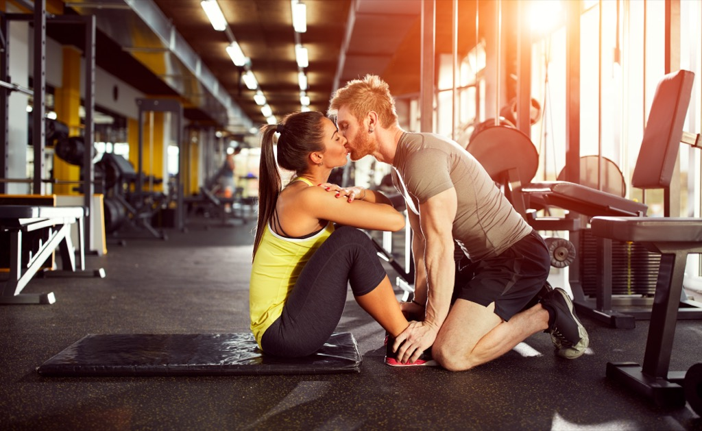 a couple kissing and exercising in the gym