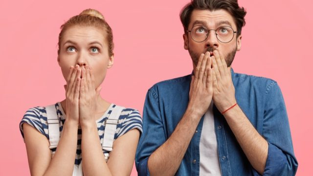 a shocked and surprised hipster couple against a pink background