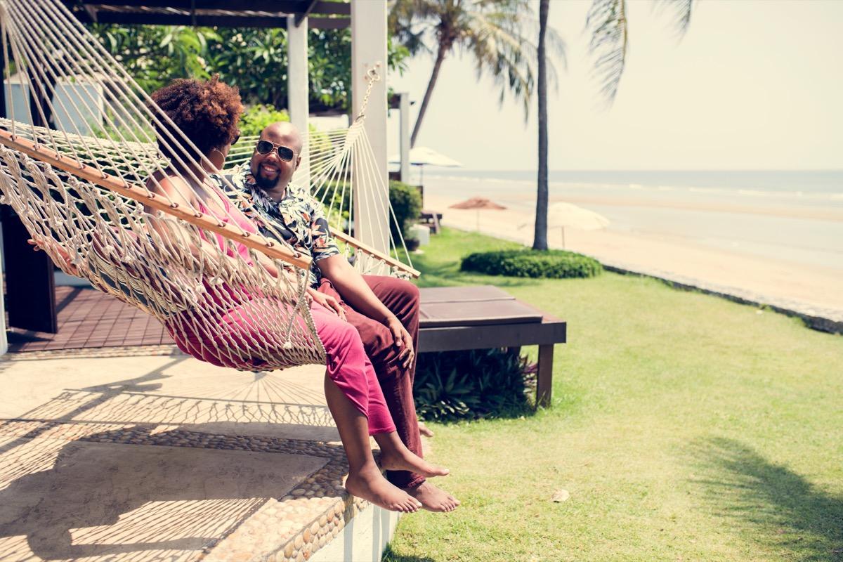 couple sitting in a hammock on a beach