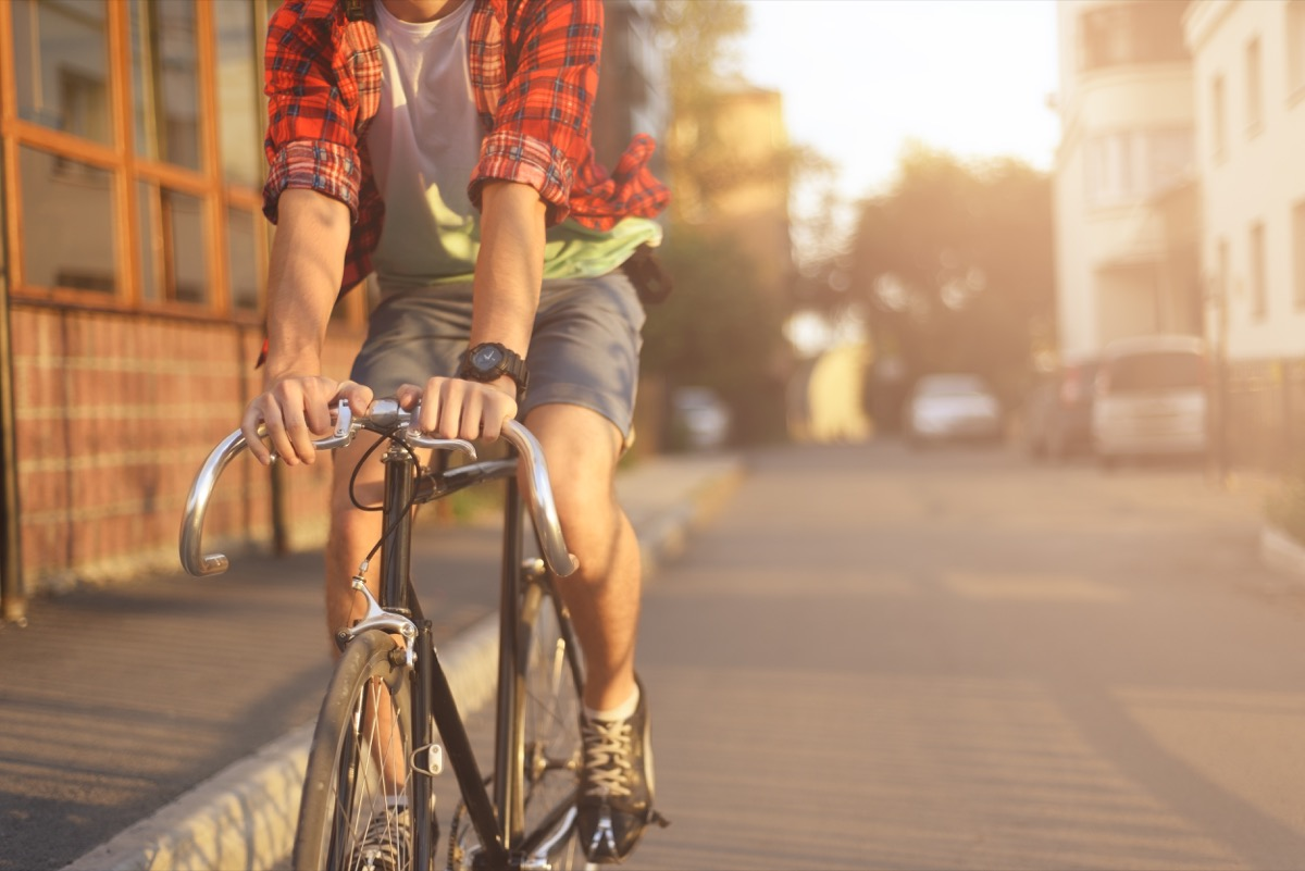 a hipster man wearing flannel and biking