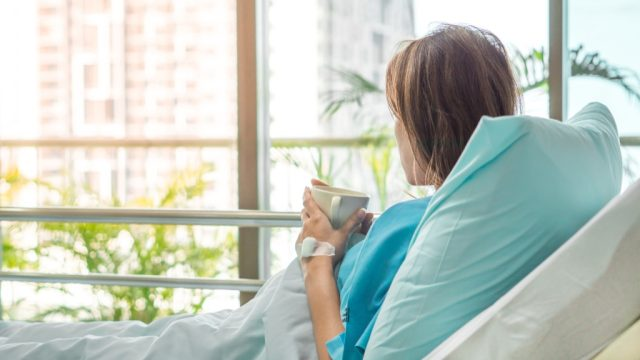Woman in a hospital bed.